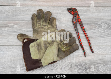 a parrot key and a pair of work gloves on a wooden table - Stock Photo