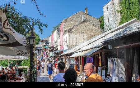 August 2013, Mostar.  Tourists relaxing & shopping in the cobbled streets in the hitsoric part of the city. - Stock Photo