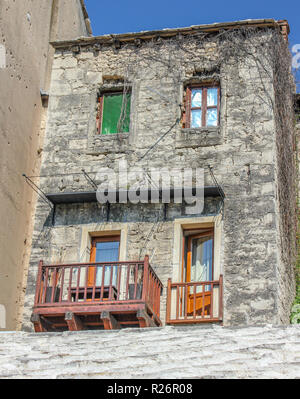 August 2013, Mostar.  A traditional old stone house with balcony terrace in the Old Town. Bullet holes from the war are visible on the wall of the nex - Stock Photo