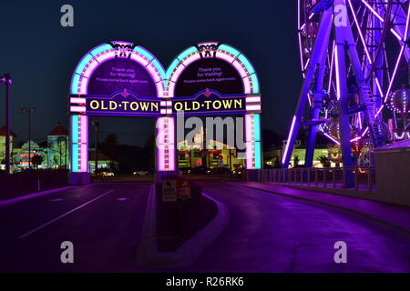 Orlando, Florida; October 31, 2018 Colofur arches and Ferris Wheel at night in Old Town Kissimmee. - Stock Photo
