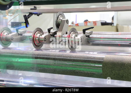 Film Roll slitting machine ; a shearing operation that cuts a large roll of material into narrower rolls - Stock Photo