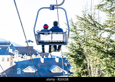 Cable car with two people going up on funicular in Sierra Nevada mountains - Stock Photo