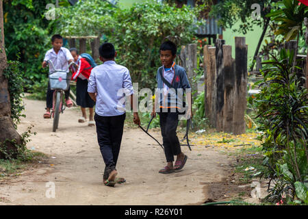 Don Det, Laos - April 24, 2018: Local children playing on a path in a remote village of Southern Laos - Stock Photo