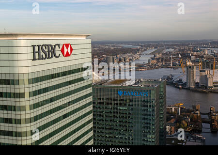 Looking across the tops of the HSBC and Barclays bank headquarters in Canary Wharf, London, with London City Airport & River Thames in the background - Stock Photo