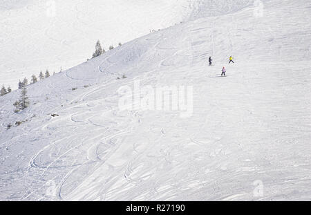 Young snowboarders on ski slope in high mountains. Winter background with snow traces and copyspace - Stock Photo
