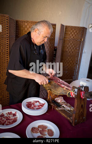 Man cutting Iberian Ham on a farm near Badajoz, Spain - Stock Photo