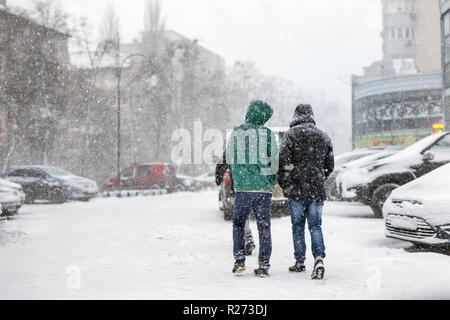 People walking through city street covered with snow during heavy snowfall. Blizzard in town at winter. Natural disasters, snow storm - Stock Photo