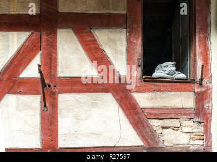 Close up of historic half-timbered truss house with white walls and red wooden beams and a stone gargoyle statue leaning on the window still and stari - Stock Photo