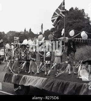 1967, young girls in costumes stand on the back of a decorated float on a truck covered with bunting, ballons and a union jack flag.as they  take part in an English village street carnival in Oxfordshire, England, UK. - Stock Photo
