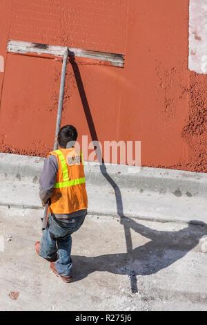 Miami Beach Florida Ocean Drive hotel construction building site work poured concrete sidewalk man laborer worker job physical - Stock Photo