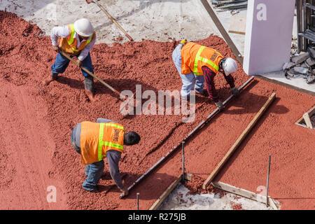 Miami Beach Florida Ocean Drive hotel construction building site work poured concrete sidewalk man men laborer worker job phys - Stock Photo