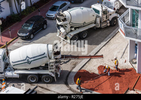 Miami Beach Florida Ocean Drive hotel construction building site work cement truck mixer pouring poured concrete sidewalk man - Stock Photo