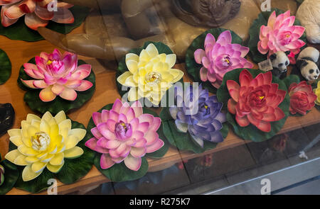 Chinese lotus flowers & other good luck talisman in window display - Stock Photo