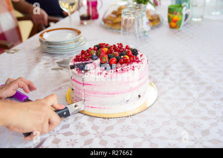 hand with knife slicing birthday cake - Stock Photo