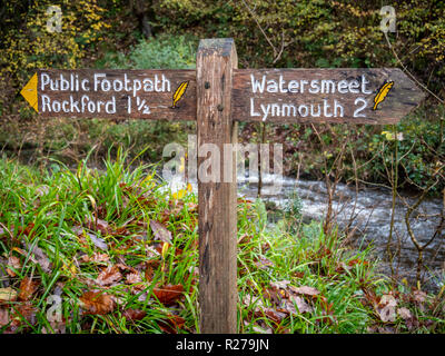 A signpost giving directions on the public footpath between Lynmouth and Watersmeet on the west lyn river valley Exmoor national Park, Devon UK - Stock Photo