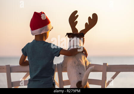 Christmas on a beach concept with boy wearing Santa Clause hat and dog with reindeer antlers headband - Stock Photo