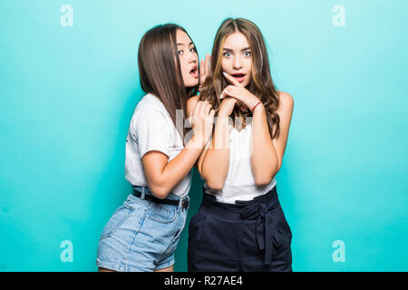 Two cheerful young girls dressed in summer clothes whispering secrets over blue background - Stock Photo
