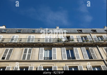 Low angle view of apartment building against blue sky in Paris, France - Stock Photo