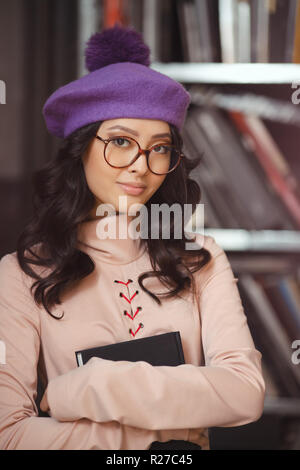 Woman studying in the library. Portrait of attractive happy asian girl holding book indoors against bookshelf. Elegant lady wearing trendy dress and c - Stock Photo
