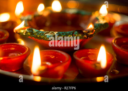 Macro shots of diyas being lit on Diwali in india - Stock Photo