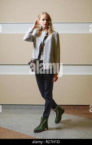 Cute student girl in jacket, jeans and boots with shoulder bag ondoors - Stock Photo