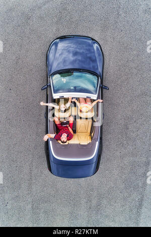 Small passenger sports convertible car with soft top down and happy family of young people enjoying lifestyle and freedom in aerial top down view. - Stock Photo