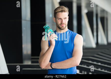 Thirst and health. Sportsman hold water bottle on stadium. Fit man with plastic flask outdoor. Stay hydrated and healthy. Water is part of healthy training. Sport and fitness. - Stock Photo