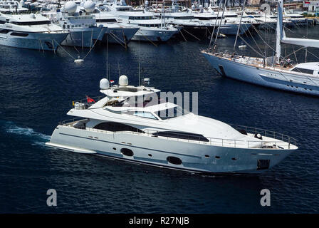 Monte Carlo, Monaco - December 08, 2009: motor yacht in navigation from port. Water craft in blue sea. Luxury lifestyle. Pleasure and sport. Summer vacation and wanderlust. - Stock Photo
