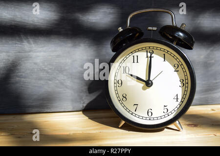 10 am/pm Back to school concept. Alarm clock on wooden with blackboard on background - Stock Photo