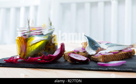 Pickled sprats in homemade marinade of olive oil, vinegar, lemon, sea salt with spices, onion and beet served with rye bread - Stock Photo