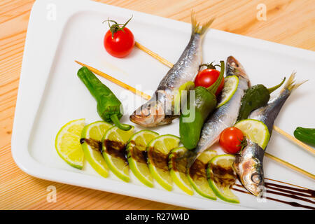 Sprats grilled with fresh vegetables, served with lime and balsamic paste - Stock Photo