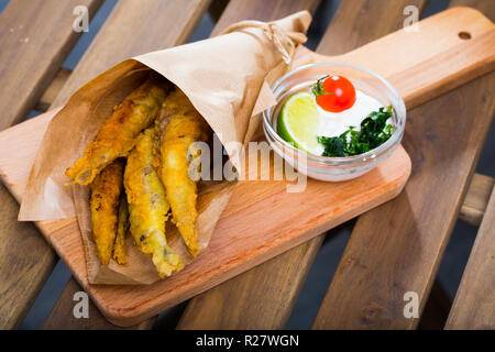 Traditional Spanish tapas - deep fried anchovies served with creamy cheese sauce, lime and greens - Stock Photo