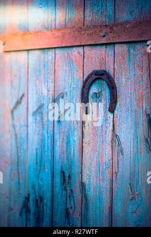 Old metal horseshoe hanging on blue wooden door - Stock Photo