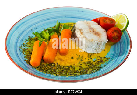 Steamed merluccius served with vegetable pate. Recipe: carrots, onion and garlic bake and beat in blender, add olive oil and salt. Fish steak 250g ste - Stock Photo