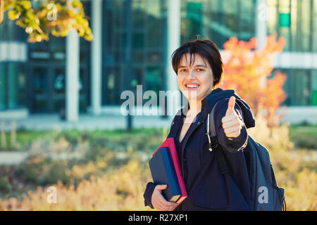 Outdoors autumn portrait of young woman student carrying backpack and books showing thumb up sign looking to camera. - Stock Photo