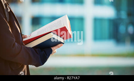 Close up portrait of student hands holding open book and reading, study education concept. - Stock Photo
