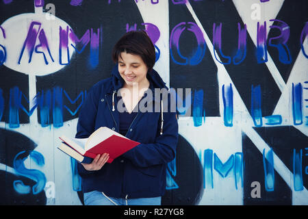 Casual happy woman student reading book, outdoors lifestyle portrait leaning back on graffiti wall background. Education concept, street art. - Stock Photo