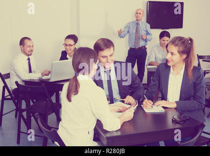 Elderly employee in charge presenting report at business meeting in office - Stock Photo