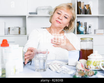 Mature woman sits at the table with medicines and bills for treatment - Stock Photo