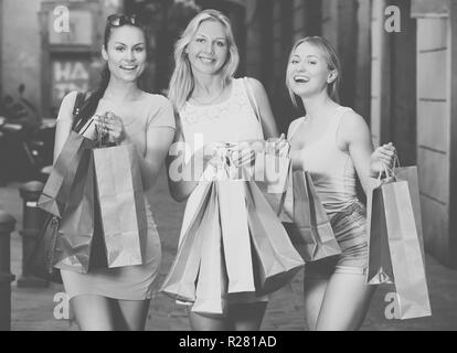 three cheerful young women looking satisfied after shopping with few paper bags in city - Stock Photo