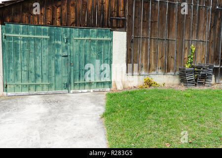 close up view of an old vintage rustic green wooden barn door on a wooden shed - Stock Photo