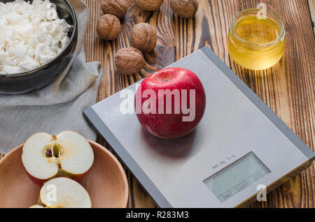 Healthy food. A red apple lies on a metal scale on a wooden table, next to it is a plate with cottage cheese, a plate with a cut apple, nuts lie and a - Stock Photo