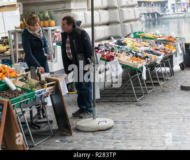 Lucerne, LU / Switzerland - November 9, 2018: man buying groceries in the city of Lucerne at an open air fruit and vegetable market stand ask the shop - Stock Photo