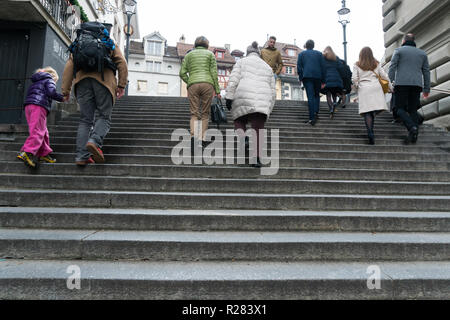 Lucerne, LU / Switzerland - November 9, 2018: many people of different age and gender rushing up and down old stone stairs in the historic city of Luc - Stock Photo