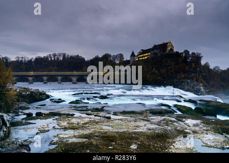 vertical landscape view of the famous Rhine Falls in Switzerland in the evening during twilight with a blurred train crossing the bridge - Stock Photo