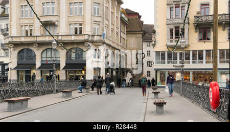 Lucerne, LU / Switzerland - November 9, 2018: many busy pedestrians and passersby and people crossing a bridge and a town square with a fruit and vege - Stock Photo