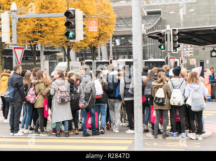 Lucerne, LU / Switzerland - November 9, 2018: many pedestrians crowd an intersection island at a busy road and crosswalk during rush hour in Lucerne i - Stock Photo