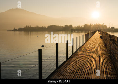long wooden boardwalk pier over water in golden evening light with a mountain landscape and people walking silhouette in the background - Stock Photo