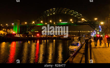 Newcastle Upon Tyne, England, United Kingdom, 17th November 2018. View from The Quayside with people walking along the River Tyne and bridges lit up at night including the High Level Bridge, the Swing bridge and the Tyne Bridge with reflections in the water - Stock Photo