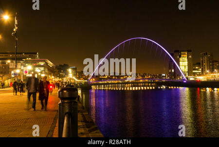 Newcastle Upon Tyne, England, United Kingdom, 17th November 2018. View from The Quayside with people walking along the River Tyne of the pedestrian Gateshead Millennium Bridge and Rank Hovis Baltic Flour Mill now Baltic Centre for Contemporary Art pit up at night with reflections in the water - Stock Photo
